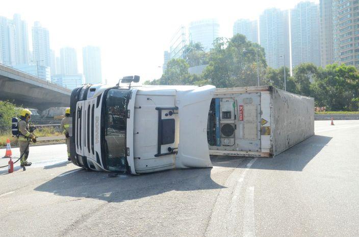 失事貨櫃車翻側橫卧路面。