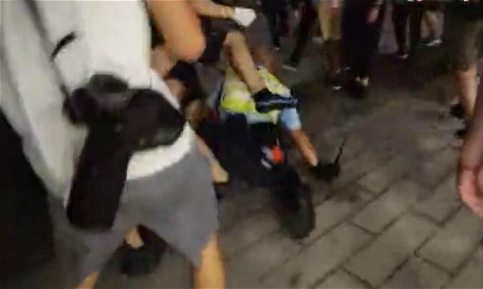 警員被打跌在地,再被示威者拳打腳踢。蘋果網影片截圖。