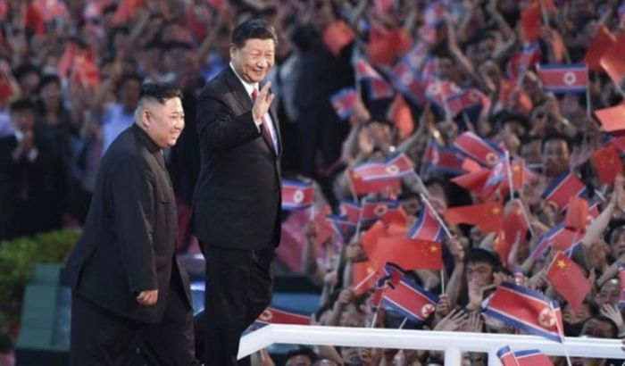 金正恩(左)盛大欢迎习近平(右)。(新华社图片)
