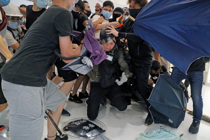 示威者圍毆警員。AP圖片