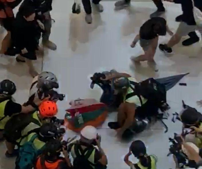 一個攝記騎在警員身上保護他。