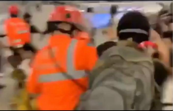 圖:救護員用手隔開男子。