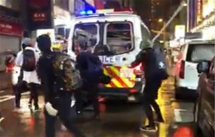 圖:示威者用鐵通狂打警車。