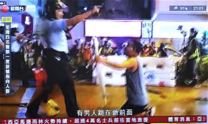 圖: 混亂中有男子撲出跪地叫警員不要開槍。有綫新聞截圖