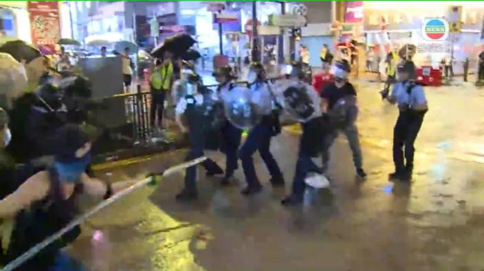 圖: 大批示威者湧出,用鐵通、竹枝追插警員。無綫影片截圖。