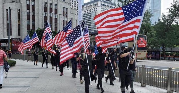 手持美國國旗的遊行人士,遊行至美國駐港總領事館。