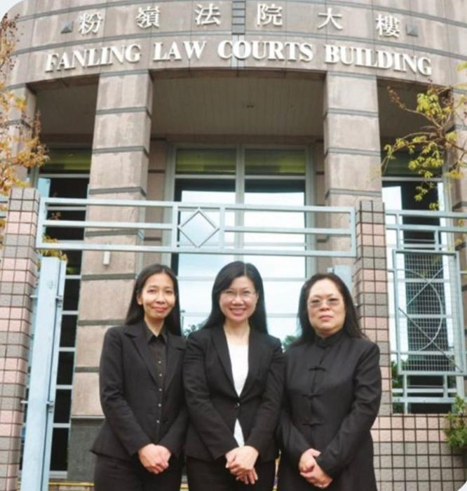 邱锦玲(右1)在粉岭裁判法院前和同事合影。