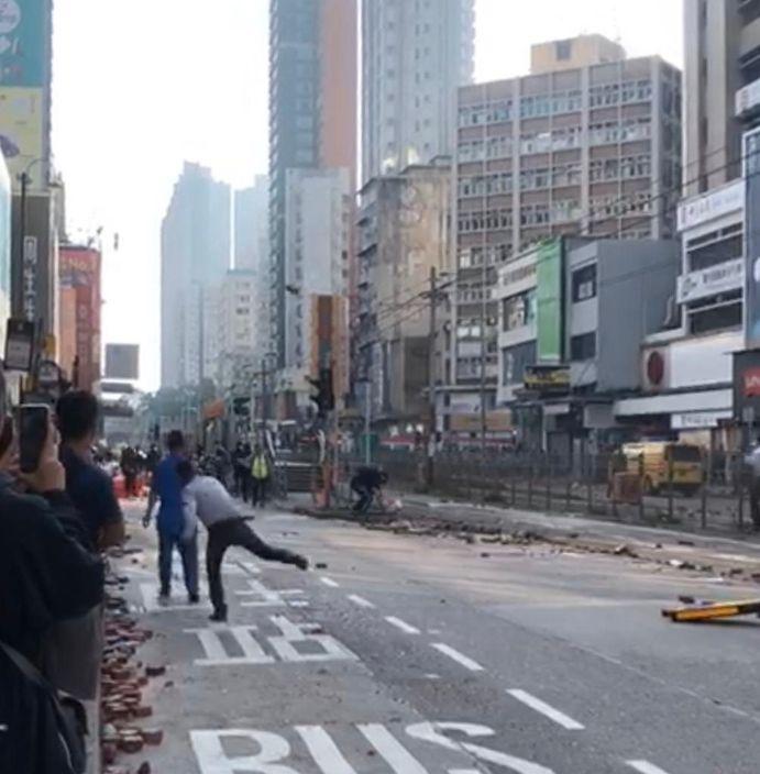 元朗大馬路有當地居民向佔路黑衣人掟石。