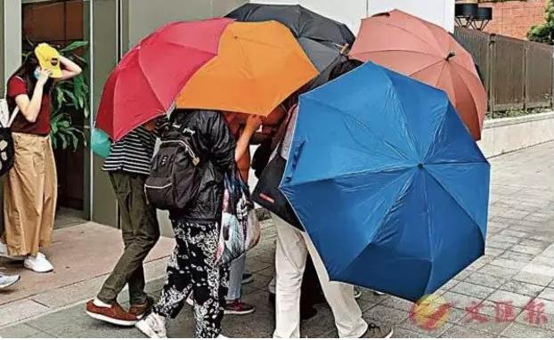 """長安劍認為,侮辱國旗者在""""雨傘陣""""的護送下離開法庭的畫面,有如是對審判者無情地羞辱和嘲諷。"""