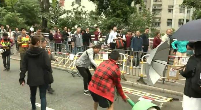 一班街坊自发搬走堵路的巴士站牌,和黑衣人争执。
