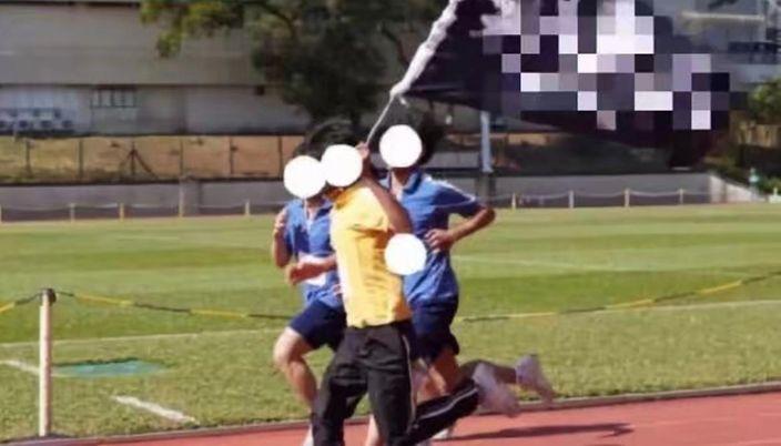 """文理书院学生在长跑赛事中,扬起""""光复香港时代革命""""黑旗"""