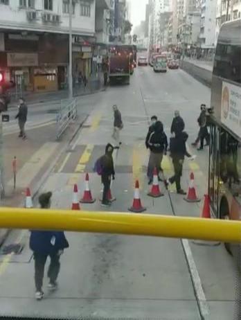 黑衣人准备向巴士喷漆