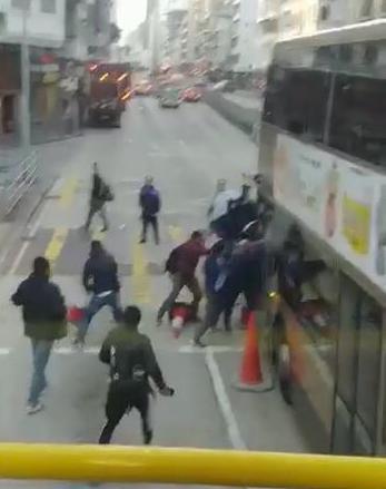 从巴士上下来的乘客,与黑衣人推撞