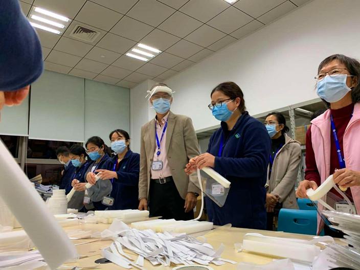 盧寵茂院長(中)和同事一起手製面罩。