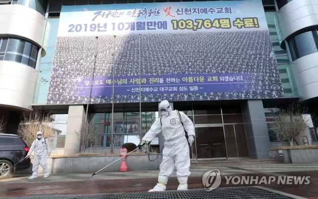 韩国政府人员在新天地教会门外消毒。