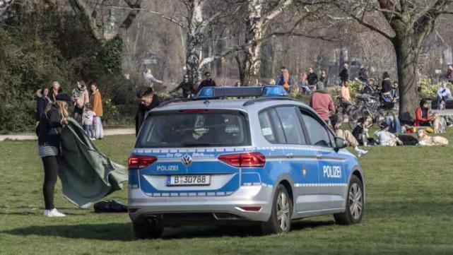 就在警車邊上鋪防潮墊曬太陽,根本不把員警當一回事。