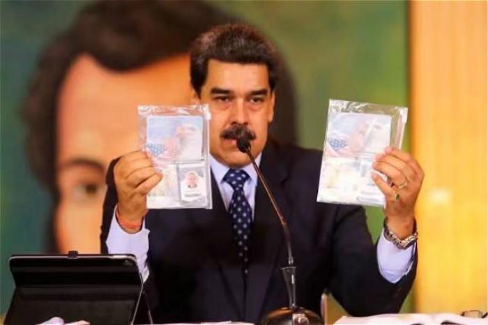 委内瑞拉总统马杜罗展示两名被捕美国公民持有的美国护照。