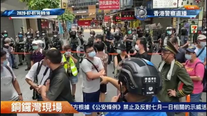 警方的傳媒聯絡人員,指向身穿螢光綠記者背心的女子,右一是快必譚得志,右二是慢必陳志全。