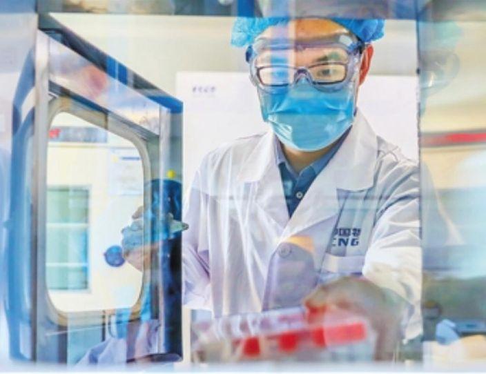 圖: 工作人員在國藥中國生物新冠疫苗生産基地質量檢定部門,從傳遞窗拿取新型冠狀病毒滅活疫苗樣品。新華社圖片