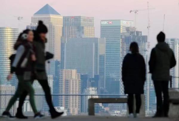 在英国伦敦,人们在格林尼治公园望向远处的卡纳里码头金融区。新华社图片