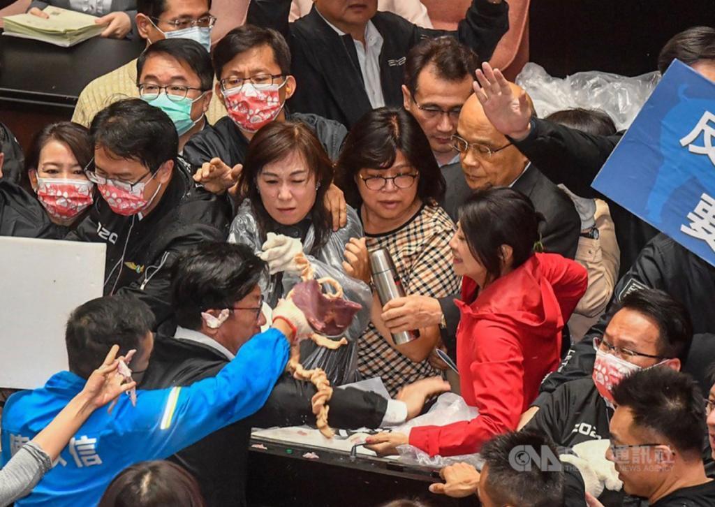 國民黨立委將內臟質向民進黨立委王美惠(中),王美惠將內臟丟回給國民黨立委。
