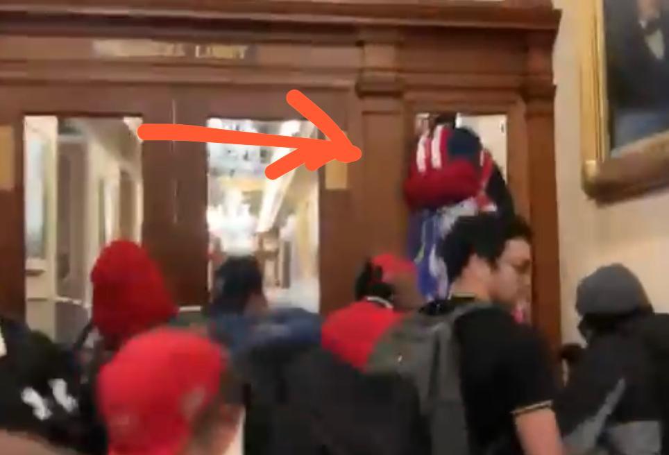 中槍女示威者在眾院議事廳門外爬高。