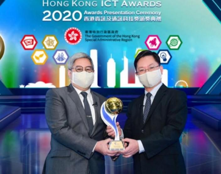 入境處處長區嘉宏(左)從創新及科技局局長薛永恒(右)手中接過「2020香港資訊及通訊科技獎: 商業方案大獎」。
