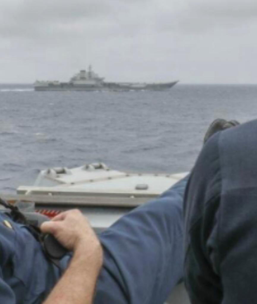 美军舰长布里格斯中校翘起双脚搭在船舷上。