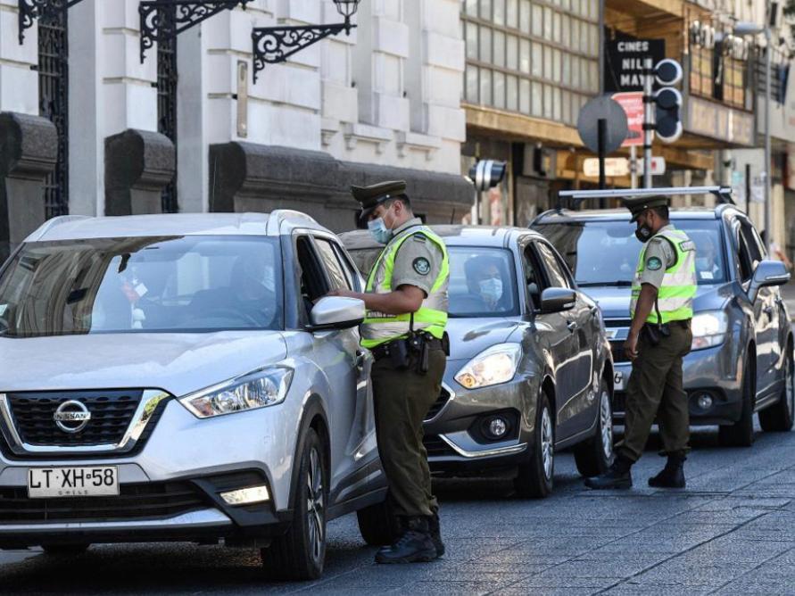 2021年3月27日,警察在智利聖地亞哥檢查「封城」措施下出行民眾的證件。新華社圖片