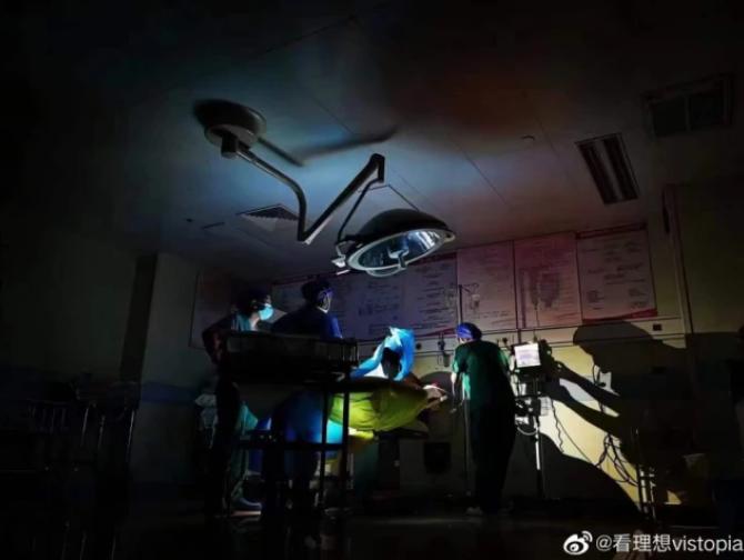 醫護人員在應急燈下為產婦接生。