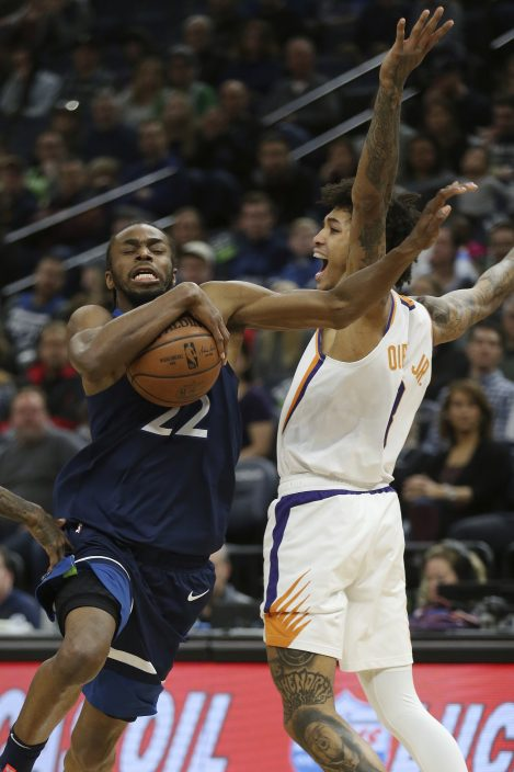 98410b68c67f Minnesota Timberwolves  Andrew Wiggins drives the ball past Phoenix Suns   Devin Booker in the first half of an NBA basketball game Sunday