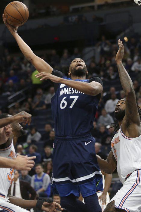 5a3d640ba65288 Minnesota Timberwolves  Taj Gibson shoots the ball against New York Knicks  DeAndre  Jordan in the first half of an NBA basketball game Sunday